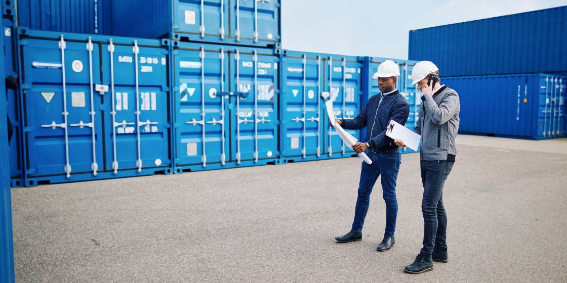 Two people review plans in front of shipping containers, illustrating one of many supply chain job opportunities